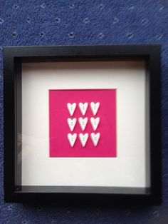 Black box framed picture. 9 white wooden hearts on a pink background.