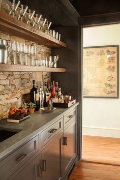 Beautiful butler's pantry with wood shelves, stone backsplash, gray cabinetry and slate counters by SB Long Interiors