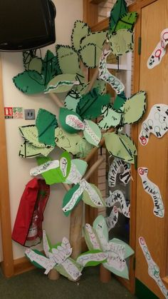 Giant tree. Trunk is a carpet roll. Leaves are cut out, hole punched and threaded by children. Children also painted caterpillars using toilet rolls to print.
