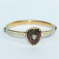A specially commissioned high carat gold ring circa 1780, the white enamelled band set with rose-cut diamonds and the head in the form of a carved garnet heart set with a central diamond. The ring is inscribed with the motto, beacoup d'impression point de blessure :  I have only feelings of love for you and wish to keep you safe from harm.