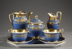 "A First Empire Paris Porcelain set, called ""tête à tête"", in mat blue enamel and enhanced with gold motifs of palmettes and foliage. It consists of a tray, two cups."