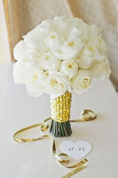 Bob Gail Special Events created this stunning bouquet with pristine white roses and a modern gold wrap. Onelove Photography.