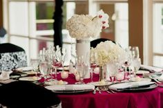 Wedding centerpiece ideas white hydrangeas,with  white and pink orchids. Table setting idea pink table clothes black chargers with white napkins wrapped around charger.