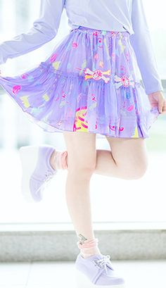 Freesize elasticated waist fully printed RAWR skirt in purple.  The skirt is overlaid in a pale purple net and is ruffled to the hem with two embroidered bone patches to the front.  The skirt is purple printed with cute dinosaurs, eyeballs, chains, skulls, lips, potions and much more.