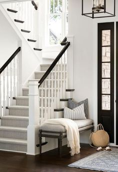 A white and gray rug sits in front of a black front door and a gray French bench positioned against a small staircase wall. Front Door Entryway, Entry Stairs, Front Door Decor, Front Entry, Small Staircase, White Staircase, Staircase Wall Decor, Hallway Art, Staircase Makeover