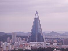 View of Pyongyang - Ryugyong hotel in construction - North Korea View from the Juche Tower in Pyongyang Dit punt - gebouw is een hotel in wording ... reeds jaren wordt eraan gewerkt! Sinds 1987. Wegens financiële problemen geraakt het gebouw niet afgewerkt. Er zijn 105 verdiepingen. Hoogte 330 meter. After 16 years the construction of the Ryugyong Hotel. The 330 Meter high building has 105 floors and is supposed to be a hotel. Construction started in 1987