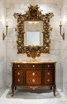 Antiques make a one of a kind powder bath. Here a 19th century French marquetry commode with gilt bronze mounts is paired with a 19th century Italian carved giltwood mirror.