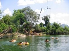 Tube the river in Vang Vieng, Laos! There are bars lining the river, zip-lines, swinging ropes, volleyball & MORE!!