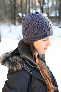 """A simple ribbing evolves into faux cables (requiring no cable needle) that create waves on top of a garter-stitch foundation in this seamless hat. The """"waves"""" converge at the top of the hat in a radiating flower shape."""