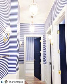 Extraordinary hallway with ink/navy horizontal striped wallpaper and doors painted to match. Very bold! Mark D. Sikes