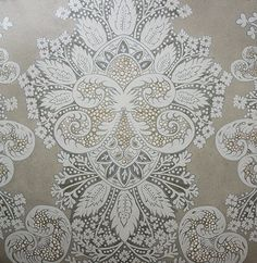 Rococo Metallic Wallpaper A wide width damask wallpaper inspired by Indian block prints and rococo motifs designed by Melissa White. Printed in white and pewter on a semi reflective metallic gold background.