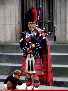 A very handsome and regal-looking Scottish piper, and two naughty boys...