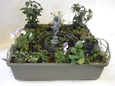 Plastic container for a fairy garden...love the figure in the center