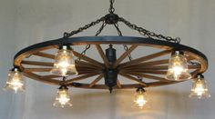 These custom, hand-crafted wagon wheel chandeliers with downlights by D Bar X Lighting create a rustic atmosphere in any decor. Wagon Wheel Chandelier Diy, Outdoor Chandelier, Rustic Chandelier, Wagon Wheel Light, Wagon Wheel Decor, Farmhouse Lighting, Rustic Lighting, Antler Lights, Rustic Lanterns