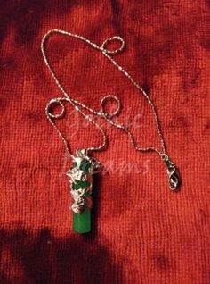 Pendant necklace with a dragon and a green stone.