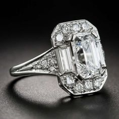 2.45 Carat Emerald-Cut Diamond Ring (GIA: E / VS1) The icy-white diamond, presumably cut during the 1930s-40s, was evidently remounted at a later date utilizing modern full-cut and sleek straight baguette diamonds on top and the original European-cut diamonds on the sides.