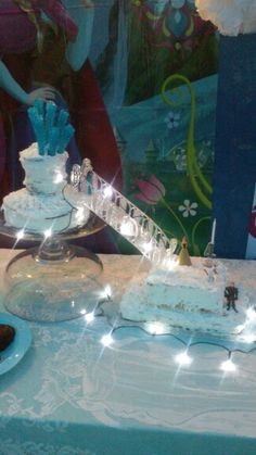 Frozen cake made with 4 different flavored levels, dollar tree figurines, battery clear lights, baker's bridge, and rock candy,