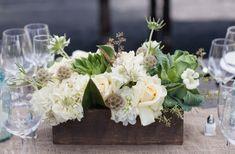 Blumenkiste mit Sukkulenten und weißen Rosen