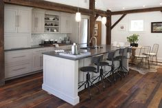 Exposed wood beams + reclaimed wood floor + industrial counter stools