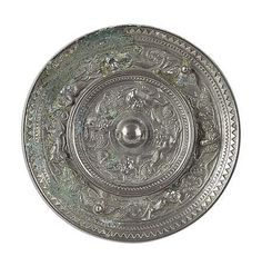 CHINESE SILVERED BRONZE MIRROR  HAN DYNASTY  decorated in relief with mythical beasts and birds  13cm diam