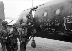 Airborne troops admire the graffiti chalked on the side of their glider as they prepare to fly out as part of the second drop of the night o...