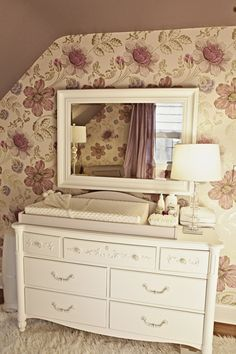 Love this painted vintage dresser, vintagey wall paper, mirror and crystal lamp. So pretty. Love how this little girl nursery feels!