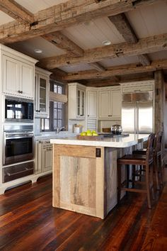 The mix of various wood tones in this kitchen — light, medium and dark — especially the pairing of stone countertops with reclaimed barn oak  --- give this kitchen rustic appeal.