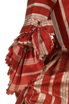 A fine striped robe à la polonaise, French, 1770s Cinnamon and ivory satin stripes, with double engageants, English back, the interior with tapes and loops to form polonaise folds; with ivory satin stomacher covered with pinked ribbon rosettes; and a finely quilted ivory satin petticoat with overall lattice design and flowerheads within triangles to the hem; together with a modern choker made to match from Valenciennes lace and ribbon (4)   Kerry Taylor Auctions