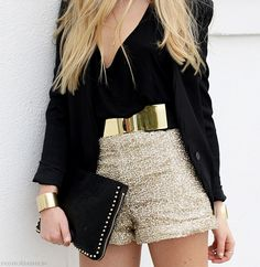 gold sequin shorts, gold belt, black tank top and black blazer with simple studded black clutch and gold bracelet