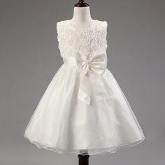 Witte feestelijke jurk met bloemetjeskant, grote sierstrik op het voorpand en aanknooplint op het achterpand. De rok bestaat uit twee lagen glitter-organza, een polyester onderlaag en daaronder een polyester binnenrokje.  Model: Manon Wit