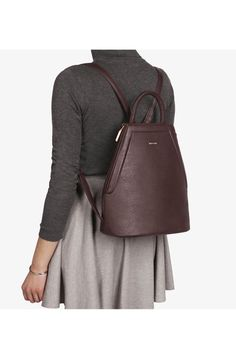 Backpack with adjustable shoulder straps. Side zippers with expandable gussets and top snap closure. Interior: zipper pocket, smartphone pocket, logo-embossed D