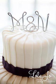 pleated wedding cake w/ purple border. monogram cake topper.
