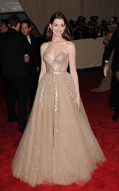 Anne Hathaway glowed in a strapless nude embroidered tulle Valentino gown.
