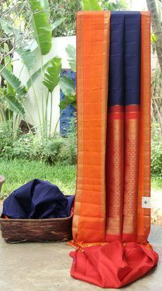 This classic piece is an indigo kanchivaram silk with gold zari work. The border is in orange and red with gold zari, while the pallu is in red with an intricate weave of gold zari making it perfec...