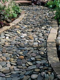 This beautiful cobblestone pathway resembles a winding river flowing through luscious garden beds on either side.