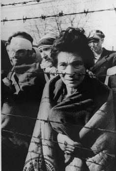 Liberated inmates behind the barbed wire fence. Auschwitz.  Pictured in the back right is Elia Fermon.