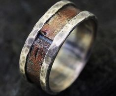 Break away from tradition and make a bold fashion statement by trading in your traditional band for this rustic men's wedding ring. This eye-catching piece sports a dark copper band at the center and is lined by two contrasting sterling silver edges.