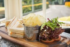 Smoked Salmon, Cream Cheese and Chive sandwich served with salad and crisps.  Lunch time idea. Lunch food. Snack. Bar meal. Bar food.
