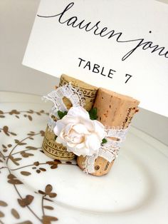 Vintage-style lace and wine corks, such pretty wedding place card holders!  Finished off with a small handmade bloom, available in 22 colors.