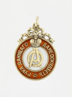 Badge of the Imperial Orphanage, 1907, Fabergé, gold, reddish-orange enamel, with Imperial monogram cypher of  Grand Duchess Olga Alexandrovna.