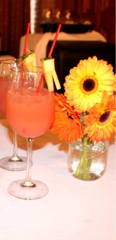"""A lovely coral colored drink, the """"Coral Oasis"""" inspired by its pleasing orange hue. Made with coconut rum, pineapple juice, a splash of cranberry juice and a splash of orange juice. Garnish with a fresh pineapple wedge and serve over ice. Very nice for an afternoon luncheon, out by the pool, a bridal shower, or a tropical themed party. ~ Photo by Celeste Ivon"""