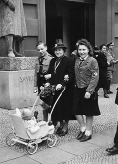 "ORIGINAL CAPTION: "" ""Aryan"" women who were the mothers of ""child-rich"" families were given extra food, home help, and holidays. They were even awarded medals. A German mother who has just received the Mother's Cross pushes a baby carriage, accompanied by two of her older children in their Hitler Youth and League of German Girls uniforms. Berlin, Germany, 1942."""