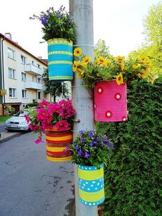 Coffee can flower pots tied to a pole or post!  Just punch two holes in back of can and run a wire or ziptie through.