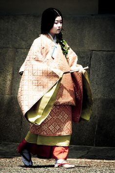 A woman dressed in traveling junihitoe for a historical parade.