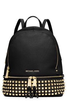 Rows of gold pyramid studs and tasseled zippers give this Michael Kors backpack…