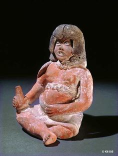 Xochipala. Clay with paint. height 7.0 cm. Seated woman holding cone shaped vessel wearing cape