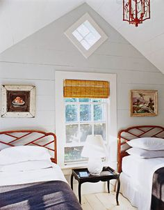 Red-painted chinoiserie headboards play off the lantern in a guest bedroom.