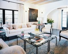 Living room with feminine detail, arched walls, and four coffee tables.
