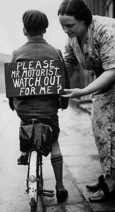 A MOTHER FASTENING A NOTICE READING PLEASE MR MOTORIST, WATCH OUT FOR ME, ONTO HER SONS BACK BEFORE HE SETS OUT ON A TRIAL BICYCLE RIDE.
