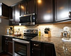 dark cabinets, stainless steel appliances, and marbled countertops